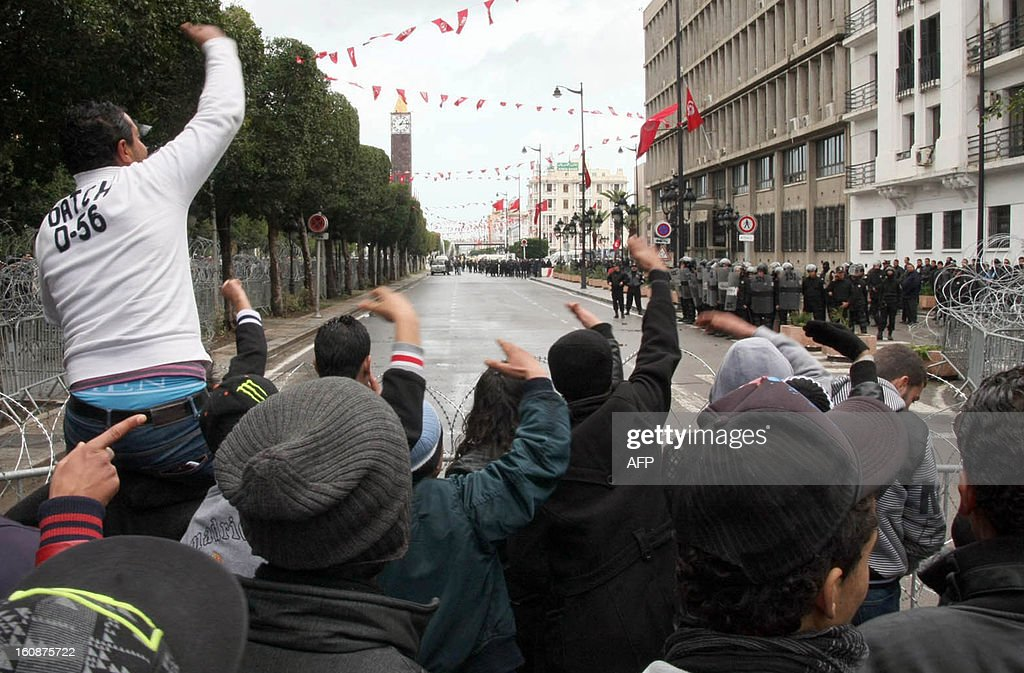 Tunisian protestors chant slogans behind barbed wire as security forces keep watch outside the Interior Ministry in Tunis, on February 7, 2013 during a demonstration against the killing of opposition figure and human rights lawyer Chokri Belaid. Police was deployed in force in the Tunisian capital amid fears the murder of the 48-year-old opposition figure could reignite nationwide violence, as the ruling Islamists broke ranks over how to defuse the crisis. AFP PHOTO / KHALIL
