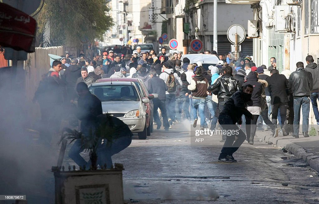Tunisian protestors clash with security forces outside the Interior Ministry in Tunis, on February 7, 2013 following a demonstration against the killing of opposition figure and human rights lawyer Chokri Belaid. Police was deployed in force in the Tunisian capital amid fears the murder of the 48-year-old opposition figure could reignite nationwide violence, as the ruling Islamists broke ranks over how to defuse the crisis.
