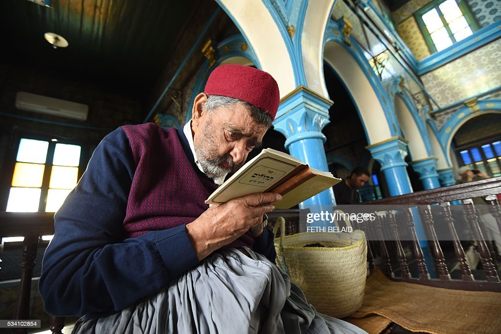 Tunisian Rabbi Attoughi reads the Torah, Judaisms most important text, at the Ghriba synagogue in the Tunisian resort island of Djerba during the annual Jewish pilgrimage on May 25, 2016. Pilgrims arrived at Tunisia's Ghriba synagogue, the oldest in Africa, expressing hope that this year would mark a turning point for the ritual despite a rise in Islamist unrest since the 2011 revolution. Djerba is home to one of the last Jewish communities in the Arab world. / AFP / FETHI