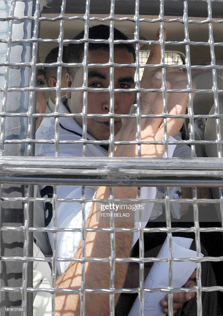 Tunisian rapper Ahmed Ben Ahmed, aka Klay BBJ, gestures behind the bars of a police vehicle as he leaves Hammamet court after a hearing as part of his trial on September 26, 2013. Klay BBJ was jailed for six months for songs judged insulting by the authorities, a verdict his supporters slammed as a sign of the Islamist-led government's growing intolerance.
