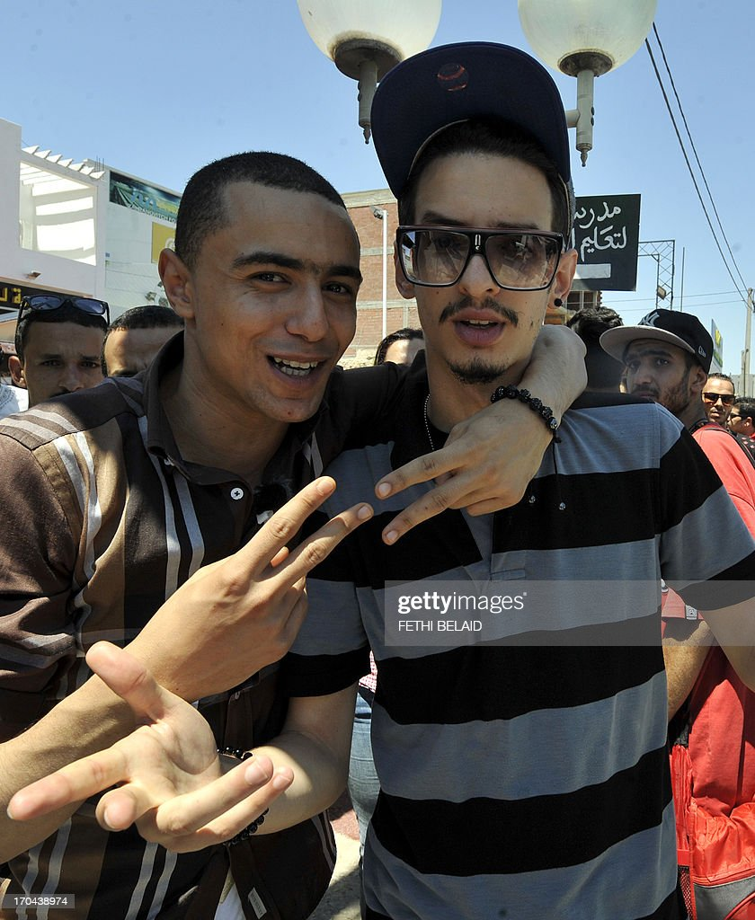 Tunisian rapper Ala Yaacoubi, better know by his rap name 'Weld El 15 (L), arrives for his trial alongside Tunisian rapper Emino (R), at the court in the Tunis suburb of Ben Arous on June 13, 2013. The Tunisian rapper risks up to seven years in prison for insulting the police has said he was 'afraid' ahead of his trial and criticised the authorities for not respecting freedom of expression. AFP PHOTO / FETHI BELAID