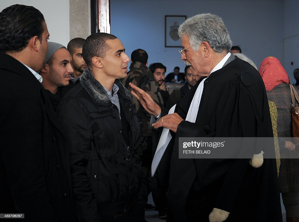 Tunisian rapper Ala Yaacoubi (C), better known by his rap name 'Weld El 15, talks with his lawyer Abada Kafi (R) upon his arrival at the courthouse for his appeal trial on December 5, 2013 in the Hammamet suburb of Nabeul. Weld El 15 has been on the run since August when he received a 21-month jail sentence, on separate charges of performing songs deemed insulting to the police. He appeals the verdict after a fellow rapper (who was convicted on the same charges) was released on appeal in September after contesting the ruling.