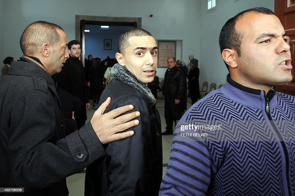 Tunisian rapper Ala Yaacoubi (C), better known by his rap name 'Weld El 15, arrives at the courthouse for his appeal trial on December 5, 2013 in the Hammamet suburb of Nabeul. Weld El 15 has been on the run since August when he received a 21-month jail sentence, on separate charges of performing songs deemed insulting to the police. He appeals the verdict after a fellow rapper (who was convicted on the same charges) was released on appeal in September after contesting the ruling. AFP PHOTO / FETHI BELAID