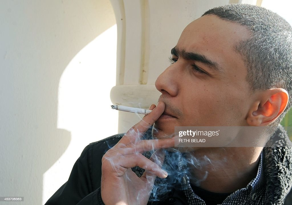 Tunisian rapper Ala Yaacoubi, better known by his rap name 'Weld El 15, smokes a cigarette as he arrives at the courthouse for his appeal trial on December 5, 2013 in the Hammamet suburb of Nabeul. Weld El 15 has been on the run since August when he received a 21-month jail sentence, on separate charges of performing songs deemed insulting to the police. He appeals the verdict after a fellow rapper (who was convicted on the same charges) was released on appeal in September after contesting the ruling.
