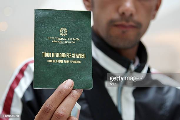 A Tunisian refugee shows on May 08 2011 in Paris the passport delivered by the Italian authorities when he arrived at Lampedusa Around 150 migrants...