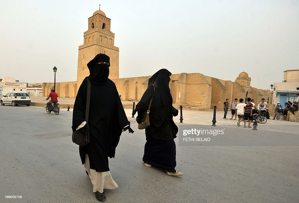 Tunisian salafi women walk in front of Okba Ibn Nafaa mosque in the city of Kairouan on May 18, 2013. Security forces deployed in numbers after Salafist movement Ansar al-Sharia called on its hardline Islamist supporters to defy a government ban on its annual congress.