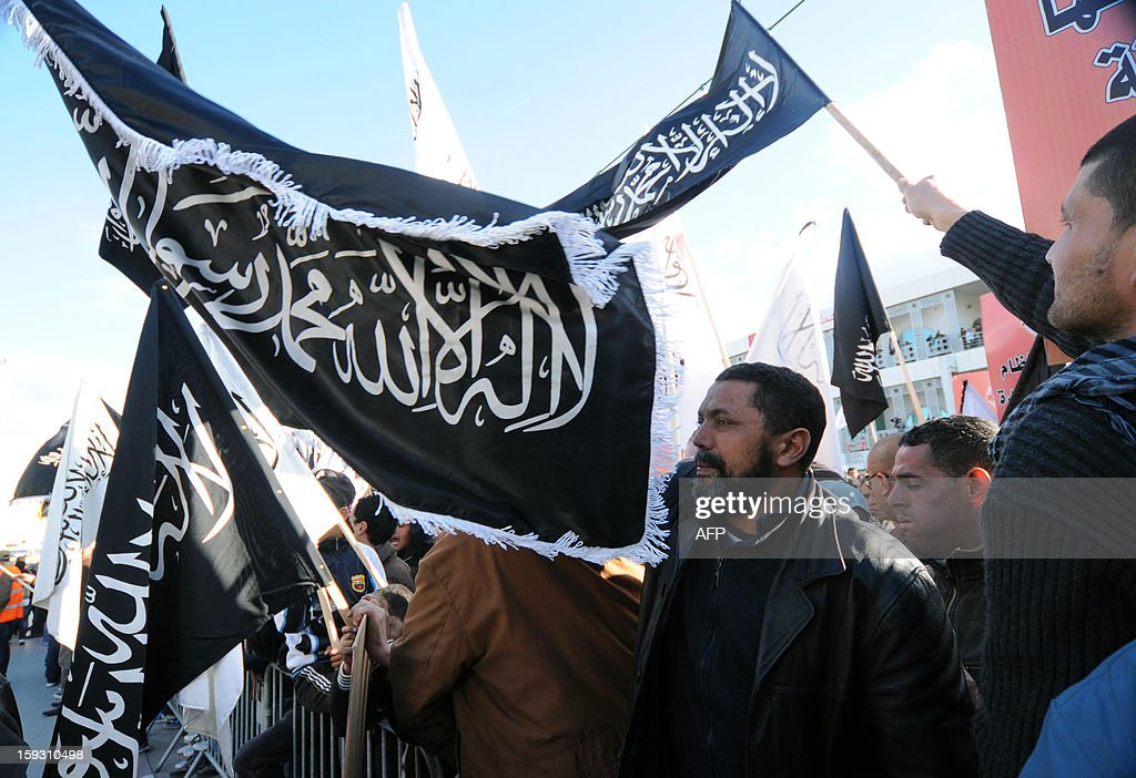 Tunisian Salafists wave black flags reading 'There's no God but God and Mohammed is his prophet' during a demonstration outside the National Constituent Assembly in Tunis to demand the application of the Islamic sharia law on January 11, 2013. AFP PHOTO / SALAH HABIBI