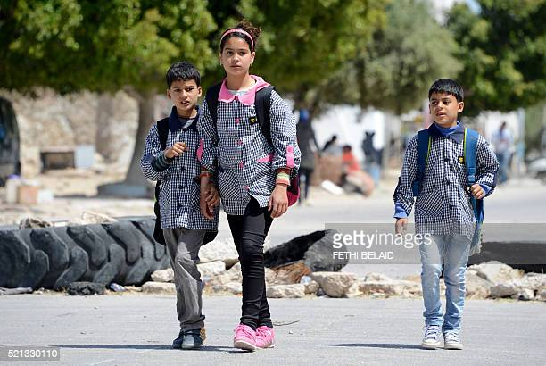 Tunisian school children walk past on April 14 2016 a road block set up by residents of the island of Kerkennah during a series of social protests...