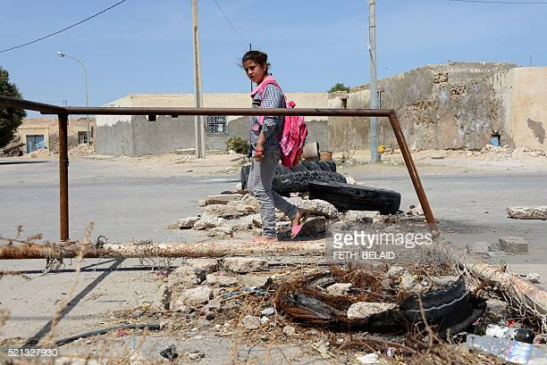A Tunisian school girl walks past on April 14 2016 a road block set up by residents of the island of Kerkennah during a series of social protests...
