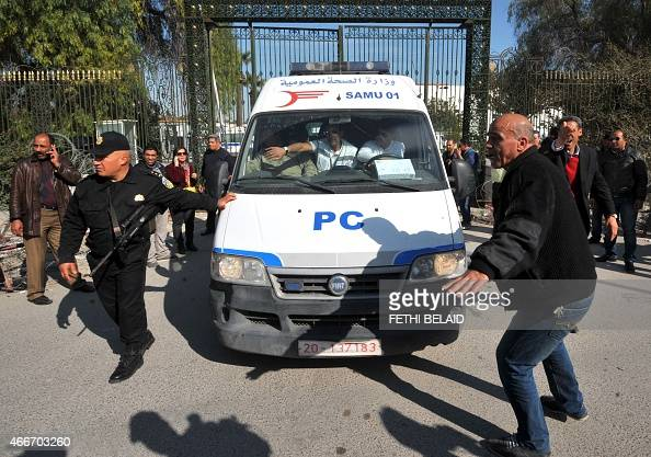 Tunisian security forces open a gate to allow an ambulance carrying wounded victims from a gunmen attack at Tunis' famed Bardo Museum on March 18...