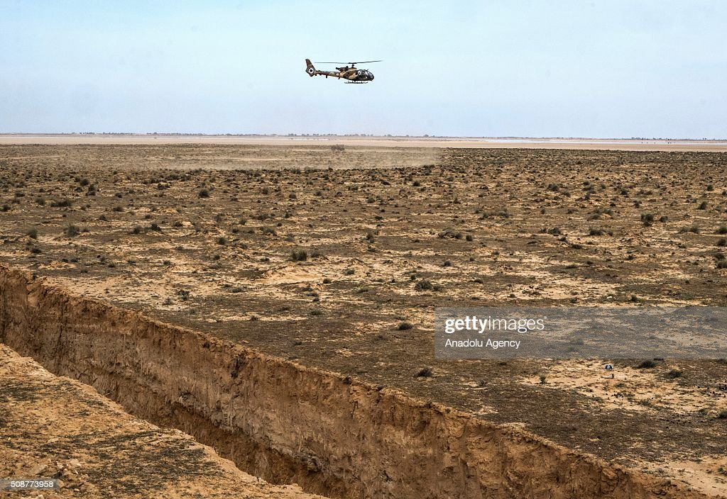 Tunisian Security Forces perform a military drill during the presentation of the Ditch, in near Ras Jedir border crossing in eastern Tunisia, close to the border with Libya, on February 6, 2016. Tunisian Defense Minister Farhat Horchani inspected the first completed part of the 196-kilometer (122-mile) ditch, which aims to render the entire border impassable by vehicles.