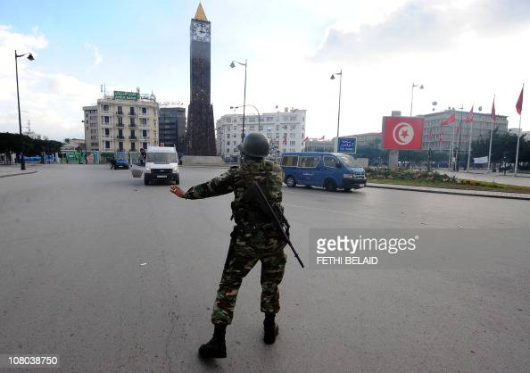 Tunisian security forces personnel clear people away during clashes with demonstrators in Mohamed V avenue in Tunis on January 14 2011 Tunisian...