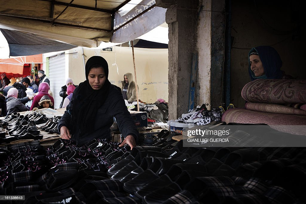 A Tunisian shoes vendor sets up her stand at a local market in the Kabaria neighbourhood on the outskirts of Tunis on February 10, 2013. After clashes with demonstrators that the interior ministry said left one policemen dead and 59 colleagues wounded, security forces remain on a state of alert with the army deployed nationwide.