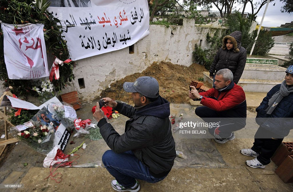 Tunisian snap souvenir photos at the grave side of assassinated opposition leader Chokri Belaid in the el-Jellaz cemetery, on February 10, 2013, in the capital Tunis. Tunisian Prime Minister Hamadi Jebali's gamble on forming a new government in defiance of his own Islamist party after the assassination of Belaid has left Tunisia in political limbo. AFP PHOTO / FETHI BELAID