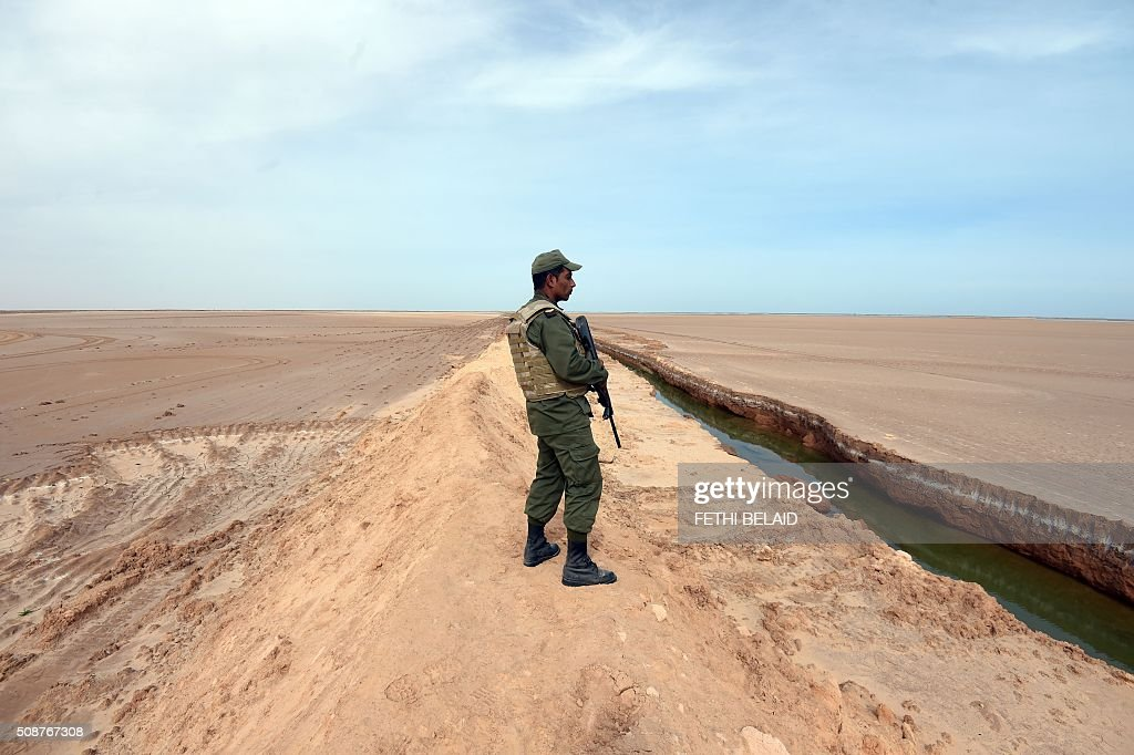 A Tunisian soldier stands in front of a trench dug along the Libyan border on February 6, 2016, near the Ras Jedir crossing point. The construction of a barrier, which includes berms and trenches, along the Libyan border from Ras Jedir on the Mediterranean coast to Dhiba was announced in 2015 after a terrorist attack on the national museum in Tunis killed 22 people. / AFP / FETHI BELAID