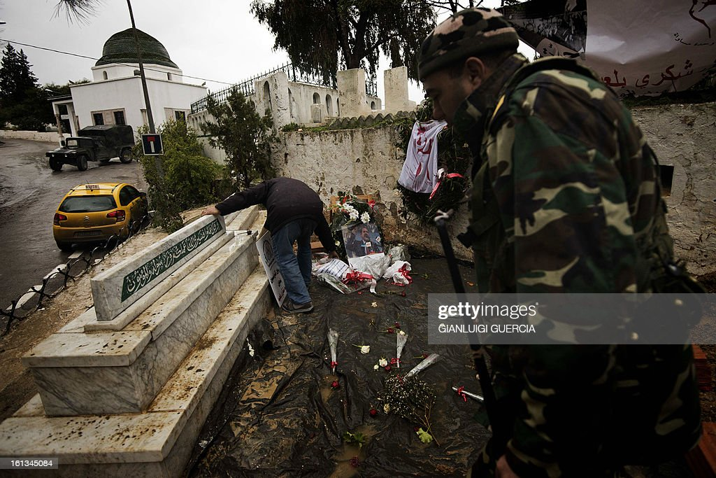 A Tunisian soldier walks past a graveyard worker fixing flowers placed on the grave of assassinated opposition leader Chokri Belaid at El-Jellaz cemetery in a suburb of Tunis on February 10, 2013. Prime Minister Hamadi Jebali's gamble on forming a new government in defiance of his own Islamist party after the assassination of opposition head Chokri Belaid left Tunisia in political limbo. AFP PHOTO/GIANLUIGI GUERCIA