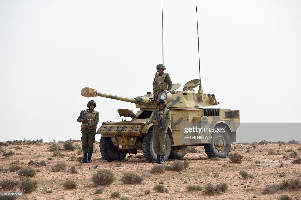 Tunisian soldiers hold a position during a military exercise along the Libyan border on February 6, 2016, near the Ras Jedir crossing point. The construction of a barrier, which includes berms and trenches, along the Libyan border from Ras Jedir on the Mediterranean coast to Dhiba was announced in 2015 after a terrorist attack on the national museum in Tunis killed 22 people. / AFP / FETHI BELAID