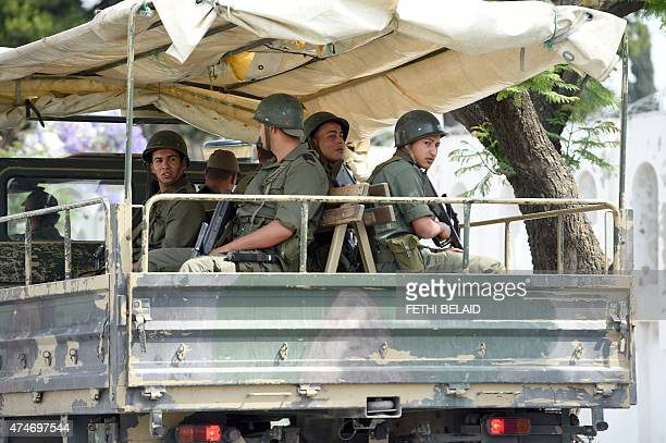 Tunisian soldiers sit on a truck as they monitor the area of the Bouchoucha army barracks in Tunis on May 25 2015 after a soldier opened fire at his...