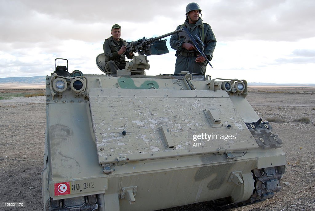 Tunisian soldiers stand on their tank as they take part in a search operation for gunmen in Dernaya Mountains in the Kasserine region, near the Algerian border, on December 11, 2012. Tunisian security forces have mounted a search operation for gunmen who carried out an attack in the Kasserine region, killing a policeman, a security source said. AFP PHOTO / ABDERRAZEK KHLIFI