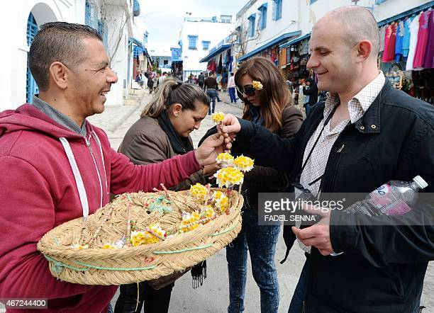 A Tunisian street vendor gives jasmine flowers to tourists in the village of Sidi Bou Said some 20 kilometers northeast of Tunis on March 22 four...