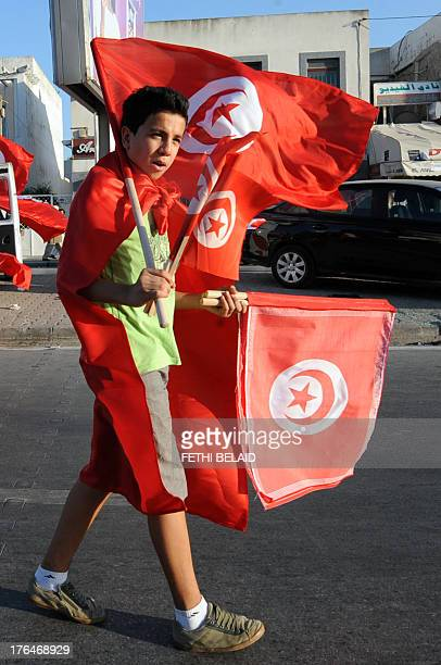 A Tunisian street vendor sells national flags to demonstrators during a protest against the country's Islamistled government in front of the...