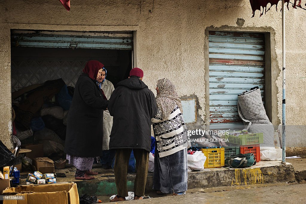 A Tunisian street vendor talks with clients in an alley of a local market in the Kabaria neighbourhood on the outskirts of Tunis on February 10, 2013. After clashes with demonstrators that the interior ministry said left one policemen dead and 59 colleagues wounded, security forces remain on a state of alert with the army deployed nationwide.