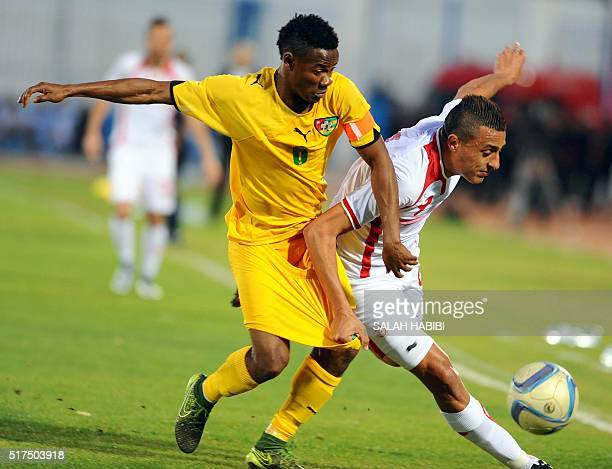 Tunisian striker Ahmed Akaichi vies for the ball with Togo's defender and captain Mama Abdoul Gafar during the African Cup of Nations 2017 qualifying...