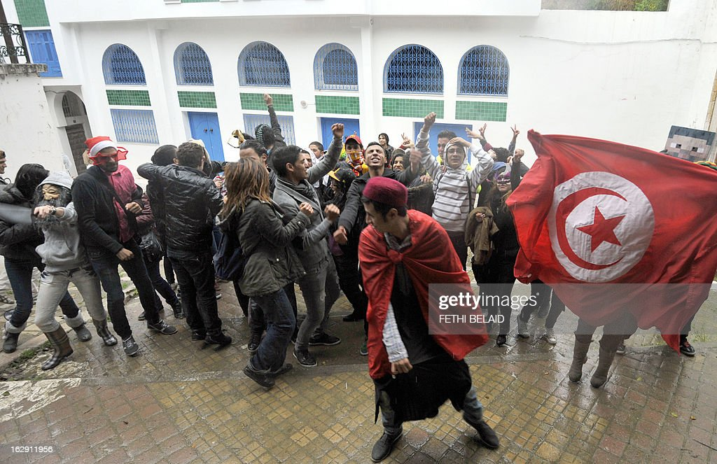 Tunisian students perform the internet video craze, the 'Harlem Shake', in front of the education ministry headqaurter on March 1, 2013. A few dozen braved the rain showing up in front of Tunisia's education ministry to perform a protest version of the 'Harlem Shake' dance craze which over the past week has infuriated ultra-conservative Muslims with their smoking, wild dancing and simulation of sexual acts, and has led to punch-ups with them and clashes with police. AFP PHOTO / FETHI BELAID