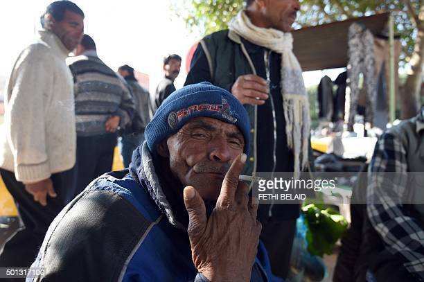 A Tunisian tea street vendor poses smoking on Mohamed Bouazizi avenue on December 14 in the impoverished central town of Sidi Bouzid three days ahead...