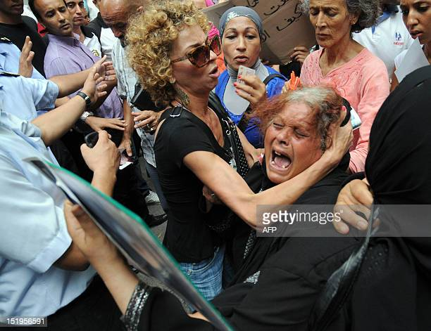 A Tunisian woman cries during a protest in Tunis on September 13 2012 as she holds a portrait of her son who was among the victims of a sunk boat...