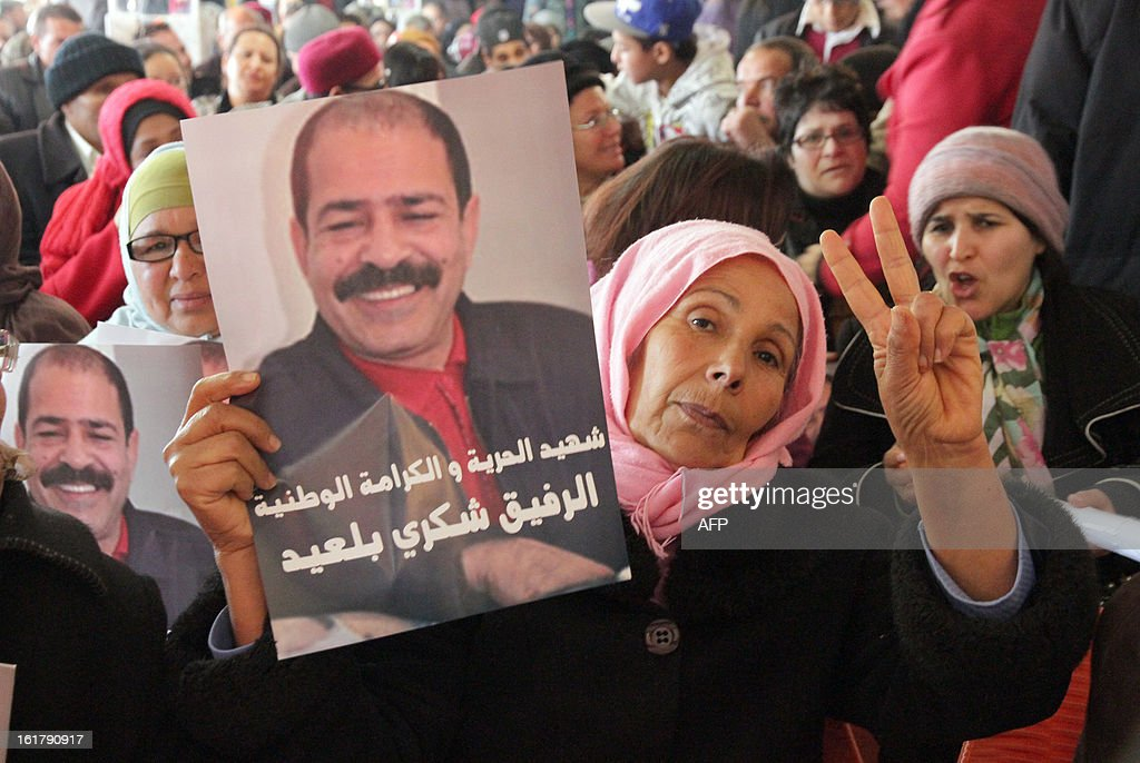 A Tunisian woman flashes the sign of victory holding a portrait of murdered opposition figure Chokri Belaid during a meeting in his memory with his widow and representatives of the Tunisia's leftist opposition alliance, Front Populaire on February 16, 2013 in Belaid's hometown Jandouba, northwestern Tunisia.