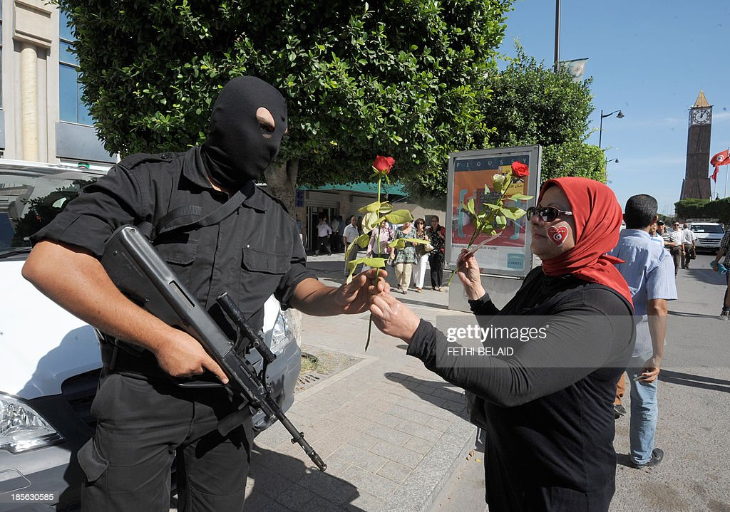A Tunisian woman hands a rose to a riot policeman as she joins opposition activists during a demonstration in Tunis' central Habib Bourguiba Avenue on October 23, 2013 demanding the resignation of Tunisia's Islamist-led government, ahead of a national dialogue aimed at ending months of political deadlock. The Habib Bourguiba Avenue was the epicentre of the January 2011 revolution that ousted former dictator Zine El Abidine Ben Ali. AFP PHOTO/ FETHI BELAID