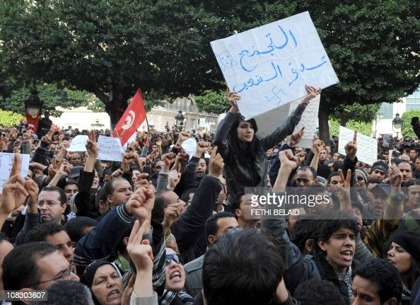 A Tunisian woman holds a banner reading 'The party of Ben Ali ennemy of the people' during a demonstration in front the Interior ministry in Habib...