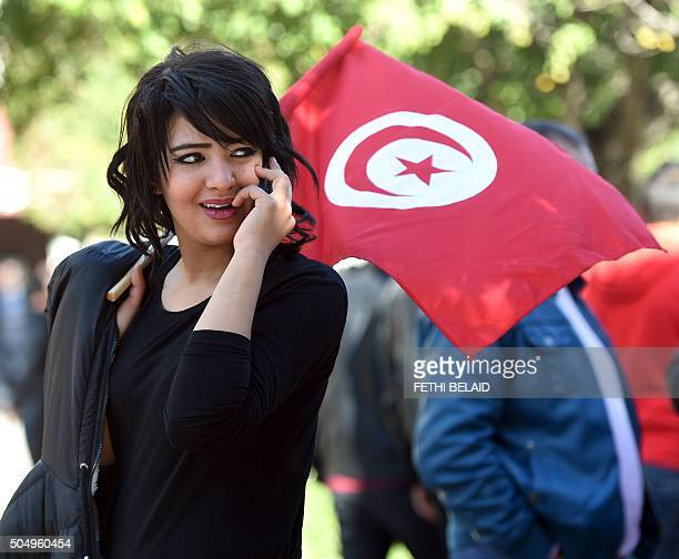A Tunisian woman holds her national flag during a rally on January 14 2016 in the Habib Bourguiba Avenue in the capital Tunis to mark the fifth...