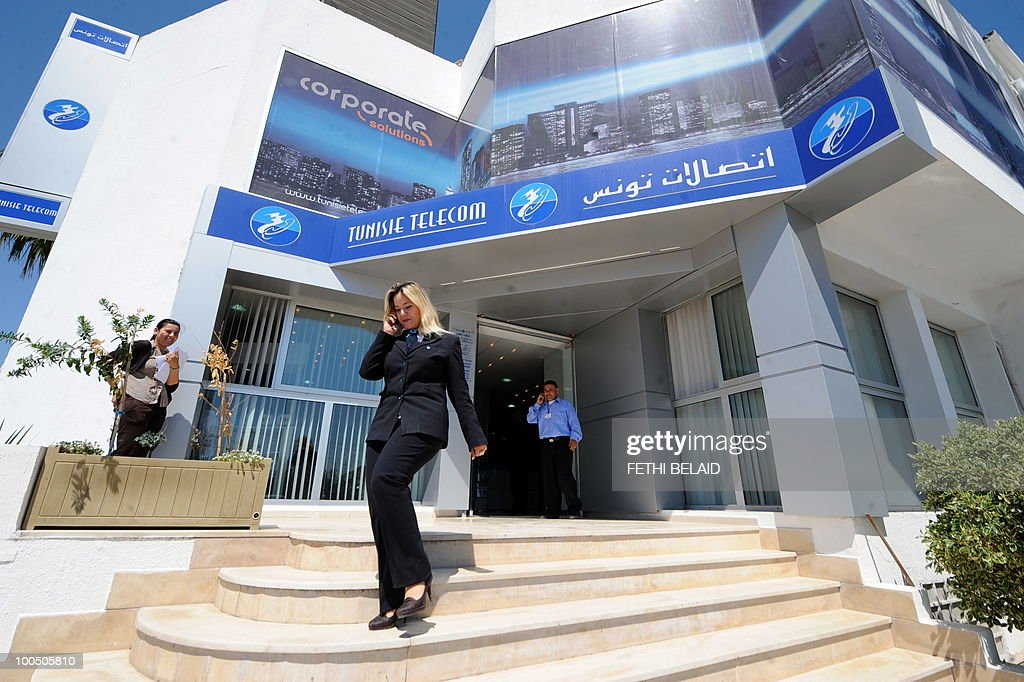 A Tunisian woman talks on her mobile phone in front of a mobile phone shop 'Tunisie Telecom' on May 25, 2010 in Tunis.