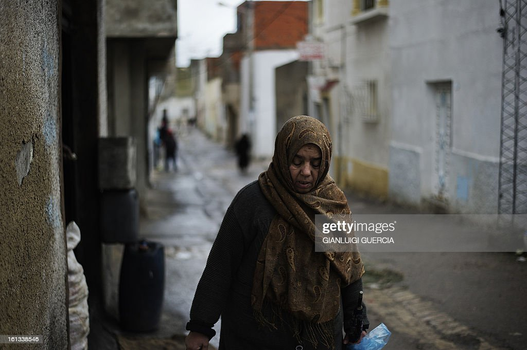 A Tunisian woman walks through a narrow alley in the Kabaria neighbourhood on the outskirt of Tunis on February 10, 2013. After clashes with demonstrators that the interior ministry said left one policemen dead and 59 colleagues wounded, security forces remain on a state of alert with the army deployed nationwide.