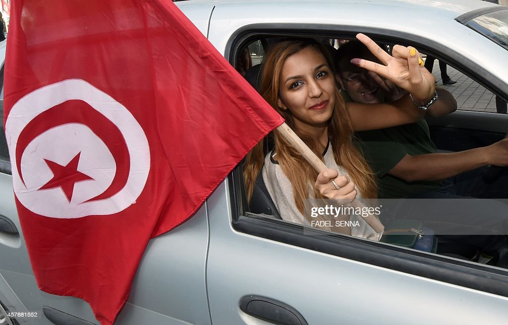 A Tunisian woman waves her national flag as she shows her inkstained finger after voting in the country's first postrevolution parliamentary election...