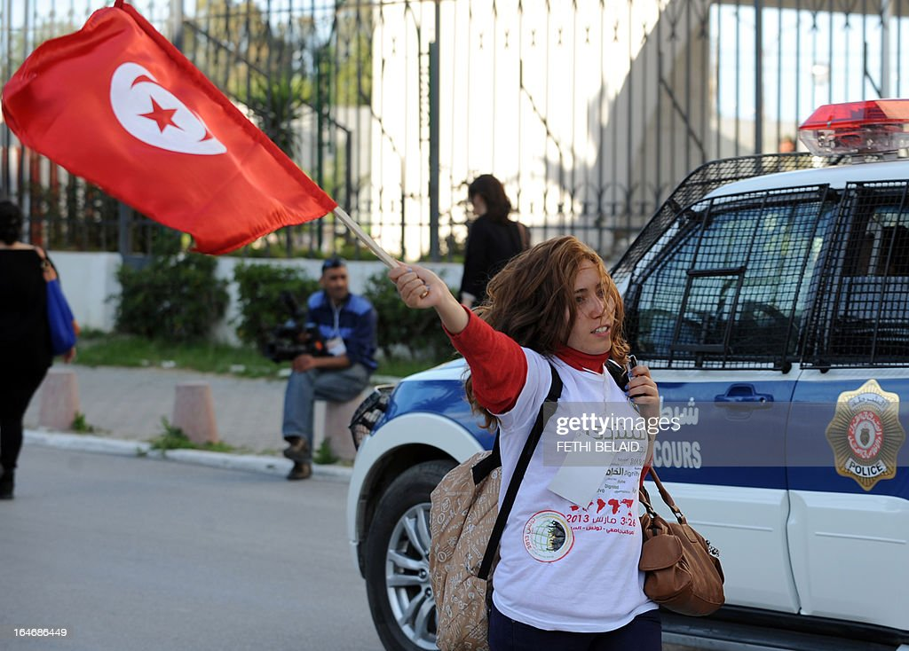 A Tunisian woman waves her national flag as she takes part in a global anti-capitalist event to demand a more just world order in the center of Tunis after the opening of the World Social Forum (WSF) on March 26, 2013. More than two years after the Jasmine revolution, tens of thousands of people are expected for the WSF, dubbed the forum of 'dignity', a watchword of the Tunisian uprising that inspired revolts across the Arab world.