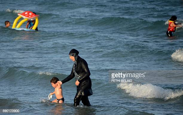 A Tunisian woman wearing a 'burkini' a fullbody swimsuit designed for Muslim women walks in the water with a child on August 16 2016 at Ghar El Melh...