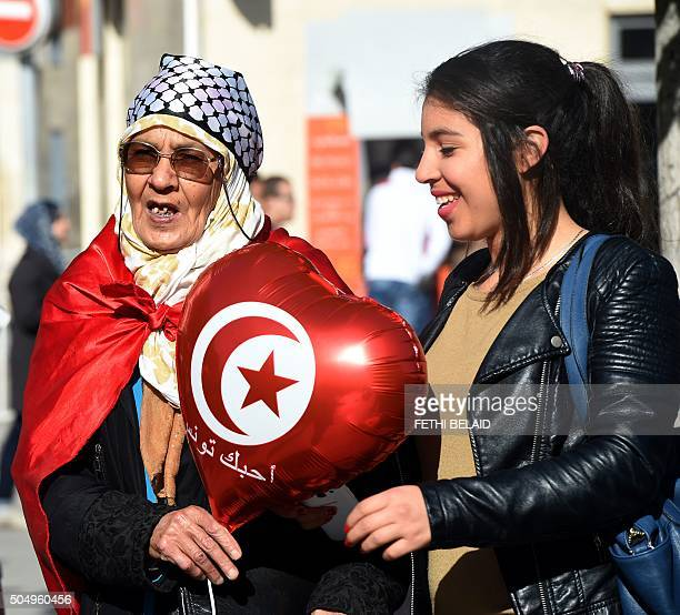 Tunisian women hold a ballon with their national flag during a rally on January 14 2016 in the Habib Bourguiba Avenue in the capital Tunis to mark...