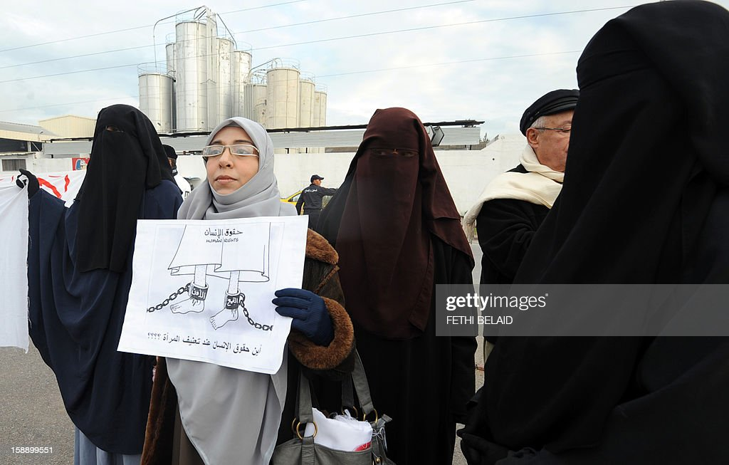 Tunisian women in niqab hold a placard in solidarity with female student wearing an islamic veil, in front to Manouba court during the trial of the dean of the faculty of arts, letters and humanities at Manouba University, Habib Kazdaghli, accused of slapping a female student wearing an Islamic veil, on January 3, 2013. Kazdaghli, whose trial has gripped Tunisia for months amid bristling tensions between secularists and hardline Salafists, attended a new hearing in the case. AFP PHOTO / FETHI BELAID