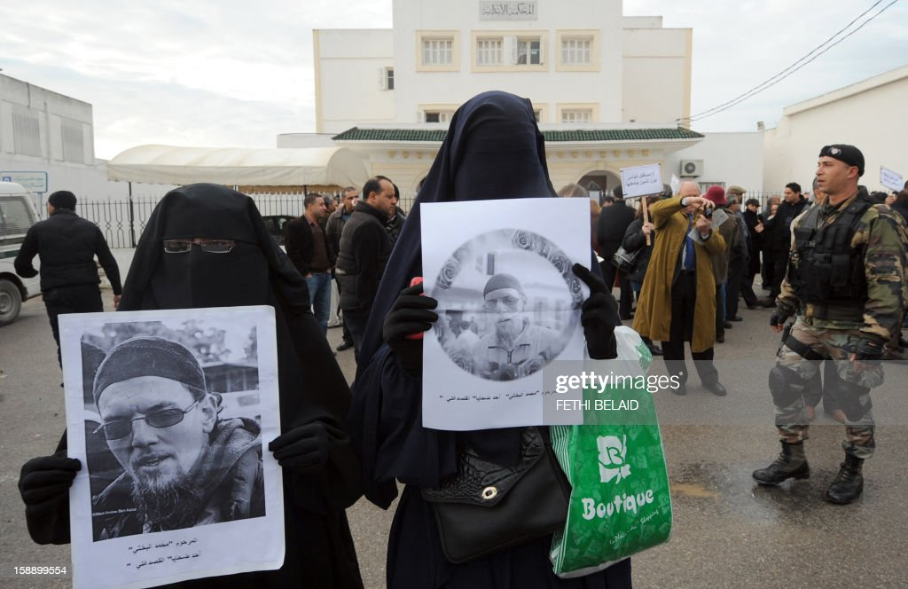 Tunisian women in niqab hold pictures of Mohamed Bakhti, former spokesman for salafist students who died in prison late last year, in front to Manouba court during the trial of the dean of the faculty of arts, letters and humanities at Manouba University, Habib Kazdaghli, accused of slapping a female student wearing an Islamic veil, on January 3, 2013. Kazdaghli, whose trial has gripped Tunisia for months amid bristling tensions between secularists and hardline Salafists, attended a new hearing in the case. AFP PHOTO / FETHI BELAID