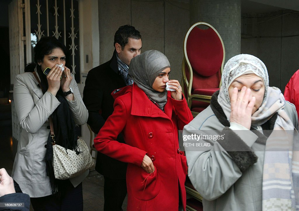 Tunisian women mourn after the killing of Tunisian opposition leader and outspoken government critic Chokri Belaid, in front of his home on February 6, 2013 in Tunis. Belaid was gunned down outside his home in Tunis, sparking angry protests by his supporters and attacks on offices of the ruling Islamist Ennahda party. AFP PHOTO / FETHI BELAID