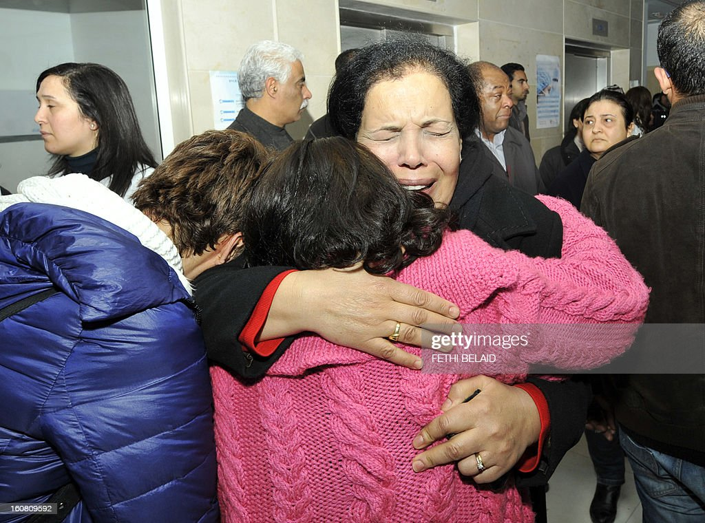 Tunisian women mourn among people gathering at the clinic after Tunisian opposition leader and outspoken government critic Chokri Belaid was gunned down outside his home, on February 6, 2013 in Tunis. Belaid was gunned down outside his home in Tunis on Wednesday, sparking angry protests by his supporters and attacks on offices of the ruling Islamist Ennahda party. AFP PHOTO / FETHI BELAID