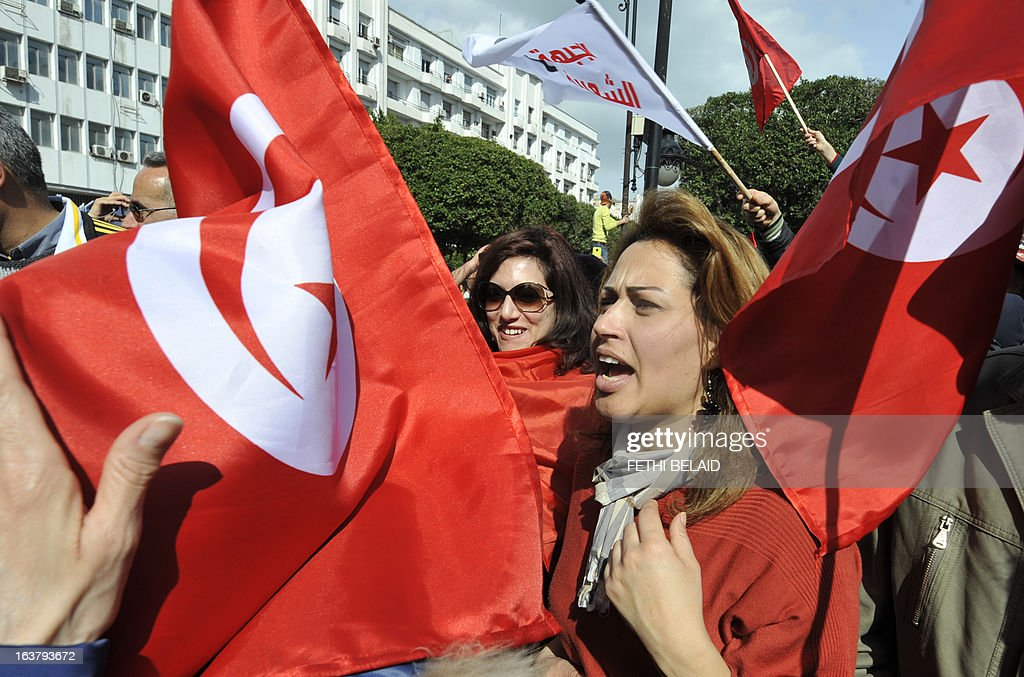 Tunisian women shoot slogans holding national flags during a demonstration to mark the 40th day of mourning after the death of anti-Islamist opposition leader Chokri Belaid on March 16, 2013 on the Habib Bourguiba Avenue in Tunis. Belaid was gunned down outside his Tunis home on February 6, 2013 with the broad daylight killing sparking clashes between protesters and police and prompting the largest anti-government demonstrations since the revolution. AFP PHOTO / FETHI BELAID