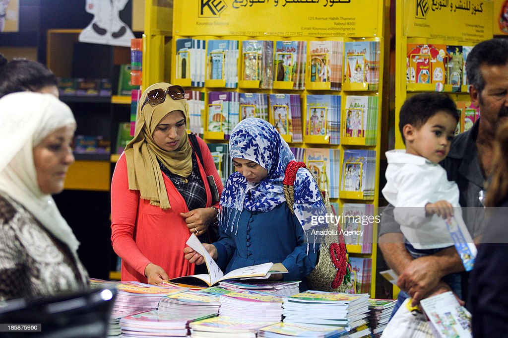 Tunisian women take a look at the books at the 30th edition of the Tunis International Book Fair that opens on October 25, 2013 in Tunis, Tunisia. 10 day event will host a thousand publishers from 31 countries.