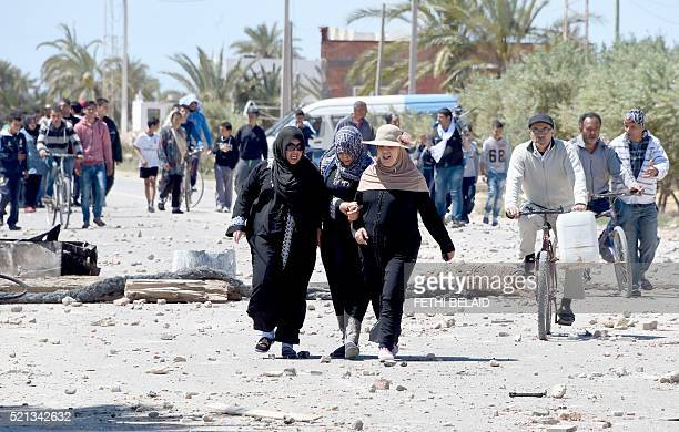 Tunisian women walk in the locality of Laataya on the island of Kerkennah on April 15 2016 after residents covered the road with stones to prevent...