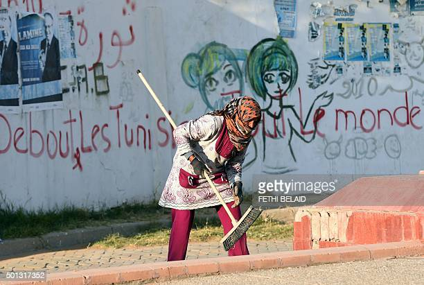 A Tunisian worker sweeps the ground on Mohamed Bouazizi Avenue on December 14 in the impoverished central town of Sidi Bouzid a few days ahead of the...