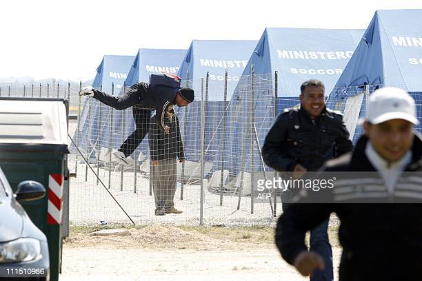 Tunisian wouldbe immigrants who were evacuated from the Italian island of Lampedusa to a reception centre in Manduria in the Puglia region jump over...