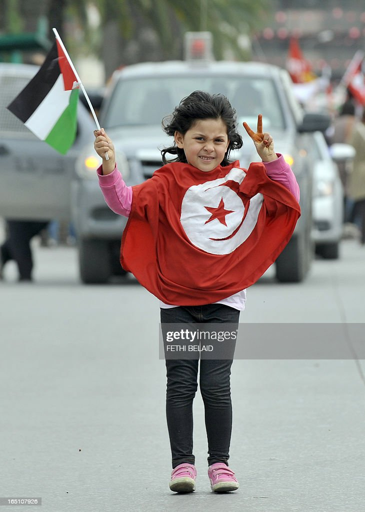 A Tunisian young girl flashes the victory sign holding a Palestinian flag and wearing a Tunisian one during a global anti-capitalist demonstration to demand justice at the closing of the World Social Forum (WSF) on March 30, 2013 in Tunis. Tunisia must find a new economic model to raise the roughly 20 percent of its people living in poverty from their quagmire, President Moncef Marzouki said on Saturday.